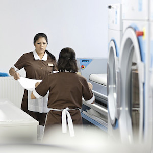 Helpful information on Choosing In-House Laundry by DISTRIBUTOR, LOCATION's #1 commercial laundry distributor, providing quality commercial laundry equipment, including washing machines, dryers, and ironers. DISTRIBUTOR can outfit your laundromat business with the best coin laundry machines. We also provide on-premises laundry solutions for commercial laundries, hotels, hospitals, restaurants, and more. DISTRIBUTOR only sells the best brands: Electrolux, Wascomat, Crossover, and PLUS. Contact us today! Your satisfaction is our guarantee.